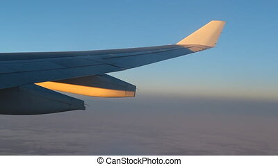 Dusk flight Golden light - Passenger jet in flight Detail of...