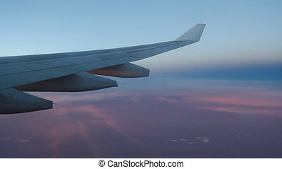 Dusk flight. Pink, purple and blue. - Passenger jet in...