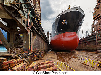 Tanker in dry dock - A large tanker ship is being renovated...