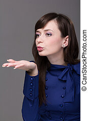 Attractive young woman blowing a kiss on a gray background