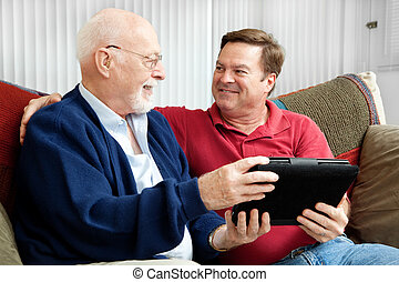 Father and Son Enjoying Tablet PC - Senior man using tablet...