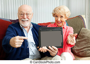 Seniors Point to Tablet PC - Senior couple pointing to a...