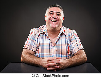 Happy mature man sitting at table - Portrait of a happy...