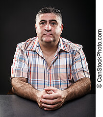 Mature man sitting at table - Closeup portrait of a mature...