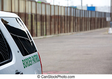 Border Fence - Border Patrol vehicle beside the large metal...