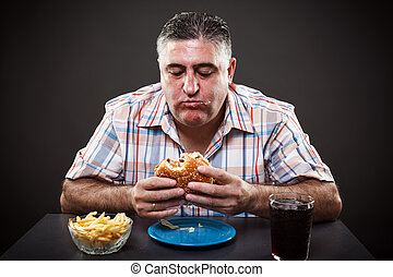 Greedy man eating burger - Portrait of a greedy fat man...