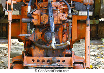 A close-up of the back of an old orange farm tractor