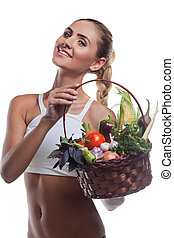 Happy young woman holding basket with vegetable. Concept...