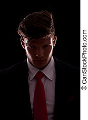 Figure of elegant young business man posing in darkness,...
