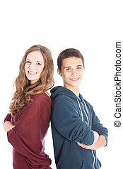 Happy teenage boy and girl standing back to back with their...