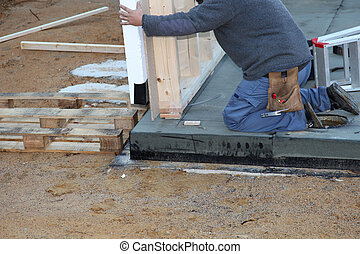 Builder installing a prefabricated wall - Builder installing...