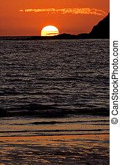 the sun in the ocean in madagascar - sunset near a mountain...