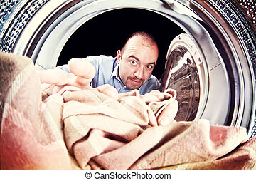 man and washing machine - portrait of man view from washing...