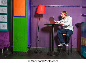 Young man sitting working on laptop in colourful location