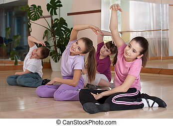 Group of children engaged in physical training indoors. -...