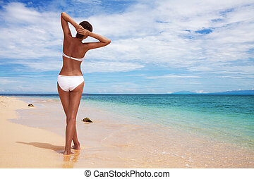 Tanned woman on the beach - Tanned woman's back relaxing on...