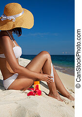 Woman applying sunscreen on the beach - tanned woman on the...