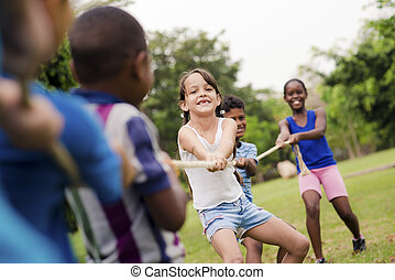Happy school children playing tug of war with rope in park -...