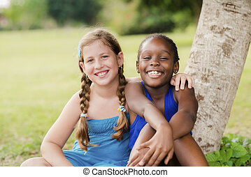 Two happy female friends hugging and looking at camera -...