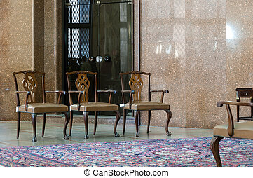 three chairs and carpet in hotel lobby