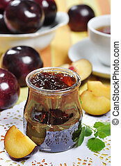 Plum jam in a glass jar and fresh fruits