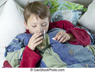 Young boy in bed taking his medicin - Young caucasian boy in...