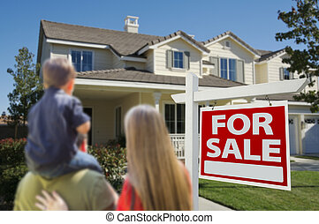 Family Looking at New Home with For Sale Sign - Young Family...