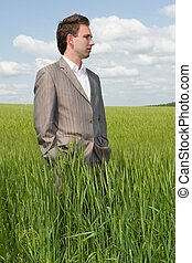 Agronomist. Businessman on a green field against the cloudy...