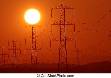 pylon sunshine - Sun above a row of electricity pylons