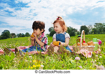 two cute kids eating lunch on picnic - two cute little kids...
