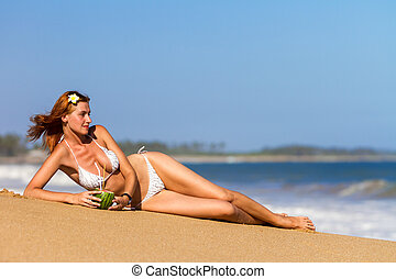 Young woman in bikini with cocktail lying on the beach