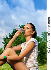 beautiful jogger resting and drinking water