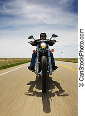 Bike travel - A biker speeding on a rural road