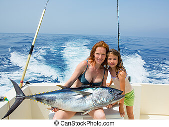 bikini fisher woman and daughter with bluefin tuna - bikini...