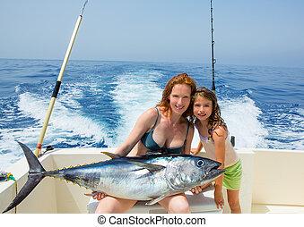 bikini fisher woman and daughter with bluefin tuna - bikini...