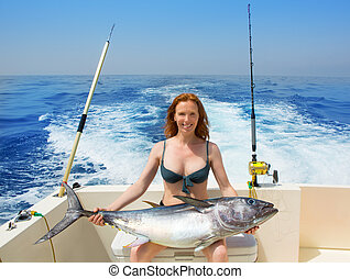 bikini fisher woman holding bluefin tuna on boat - beautiful...