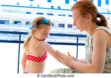 children girl with mother applying sunscreen in summer