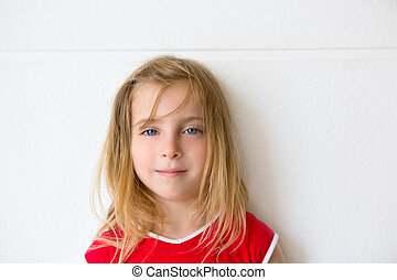 Blond beautiful kid girl smiling on white wall