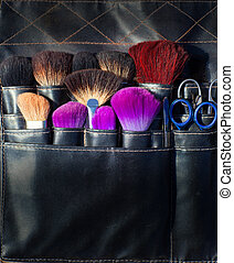 brushes scissors and tools of makeup artist in black leather...