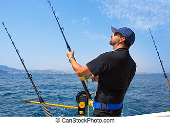 blue sea fisherman in trolling boat with downrigger - blue...
