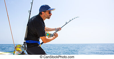 blue sea offshore fishing boat with fisherman holding rod in...