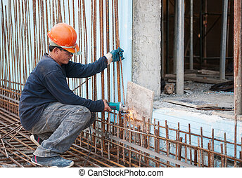 Construction worker cutting steel rods - Authentic...