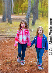 children sister girls walking at the pine forest