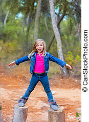 kid girl climbing tree trunks with open arms having fun in...