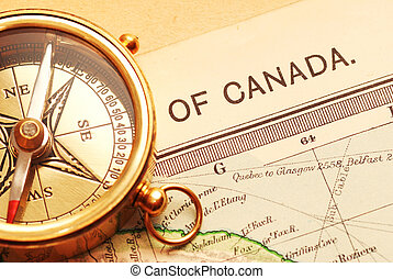 Antique brass compass over old Canadian map background...