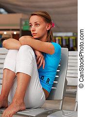 Flight delay - Woman waiting for a delayed flight