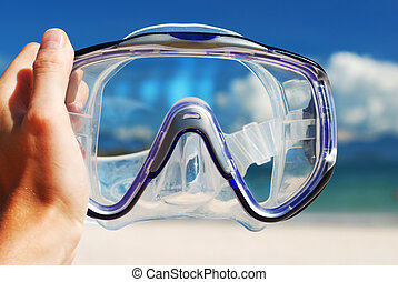 Snorkel equipment in hand against beach and sky