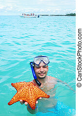 Snorkel with starfish - Snorkel man holding red starfish