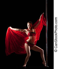 Woman posing in pole dance with red silk fabric