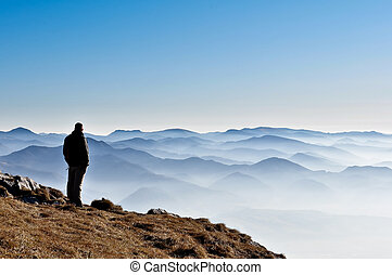 Misty mountain hills and man silhouette overlooking foggy...